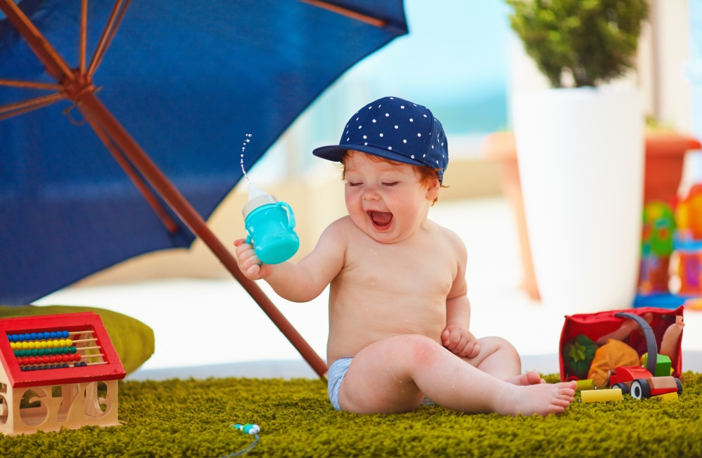 cute infant baby boy having fun outdoors at warm summer day